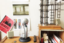 Maquettes, books and on the wall in the middle, an image of a painting by Kay Sage.