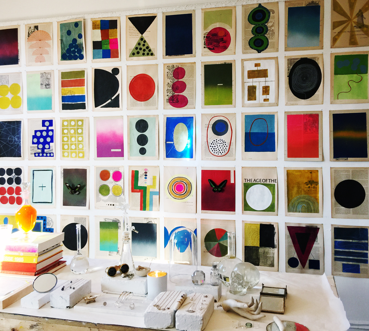 Studio View: wall of paintings on book paper and jewelry table display