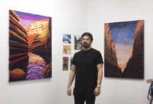 Kimo Nelson with his paintings